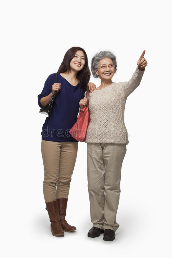 Senior mother and daughter pointing, studio shot royalty free stock photography