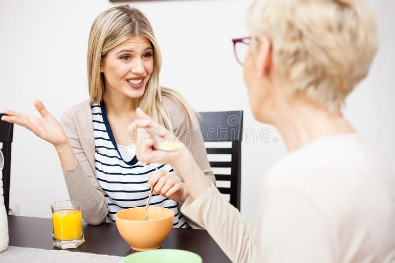 Young daughter and her senior mother eating healthy breakfast and talking. Senior mother and daughter talking and eating healthy cereal breakfast in brightly lit royalty free stock photography