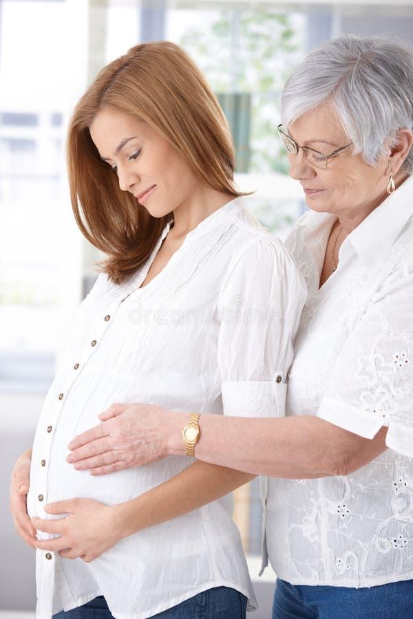 Senior mother embracing pregnant daughter smiling