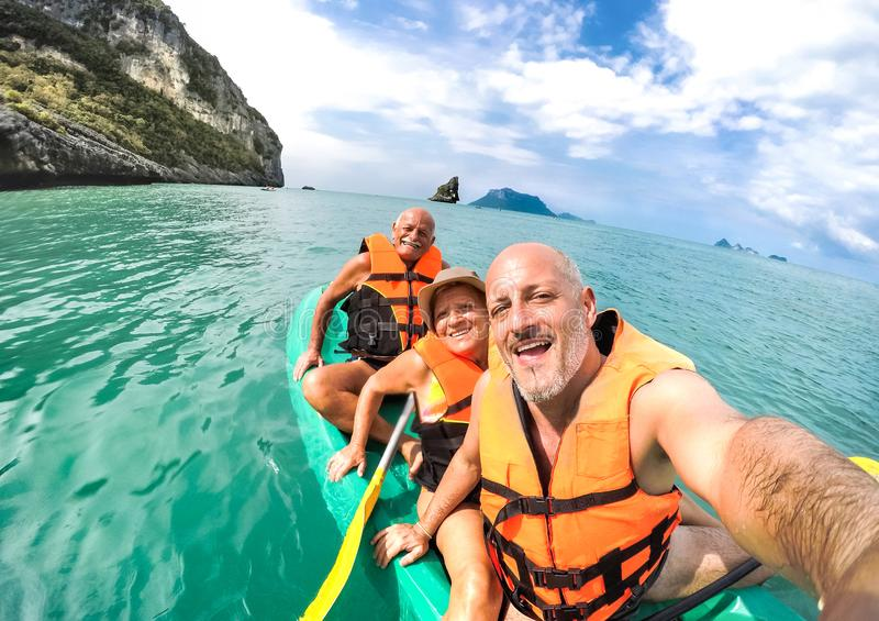 Senior mother and father with son taking selfie at kayak excursion in Thailand - Adventure travel in south east asia. Senior mother and father with son taking royalty free stock images
