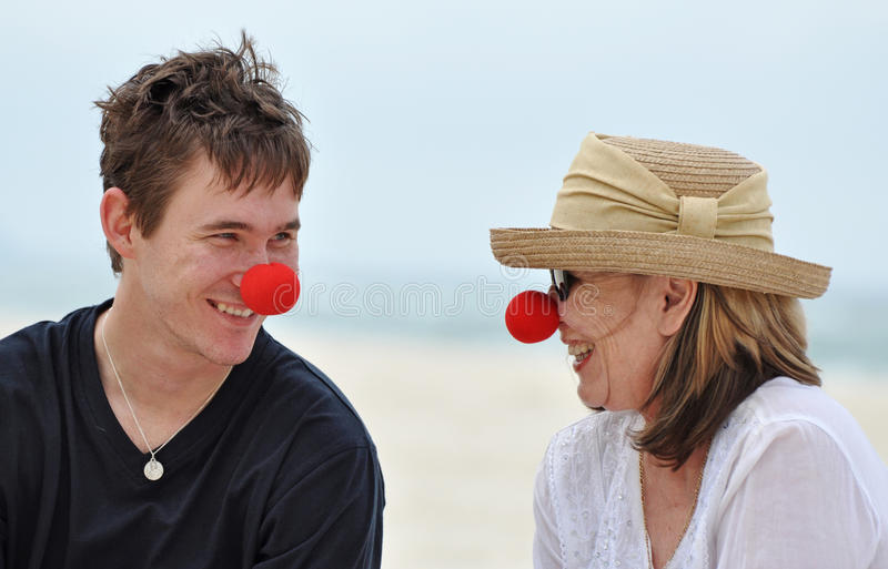 Senior mother & grown son in red noses laughing together. A happy intimate image of a mature mother with her adult son relaxing on a beautiful white sandy beach stock photo