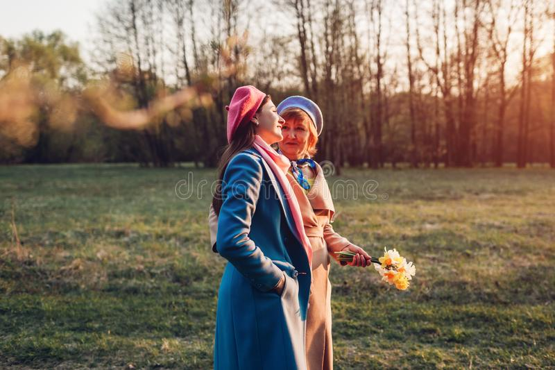 Senior mother and her adult daughter walking in spring park. Mother`s day concept. Family values. Happy senior mother and her daughter walking and talking in royalty free stock images