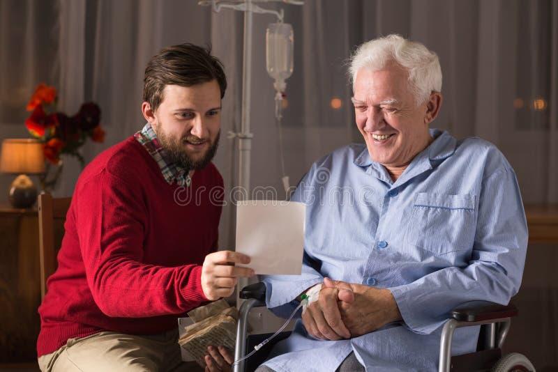 Senior na wózku inwalidzkim z synem obraz royalty free