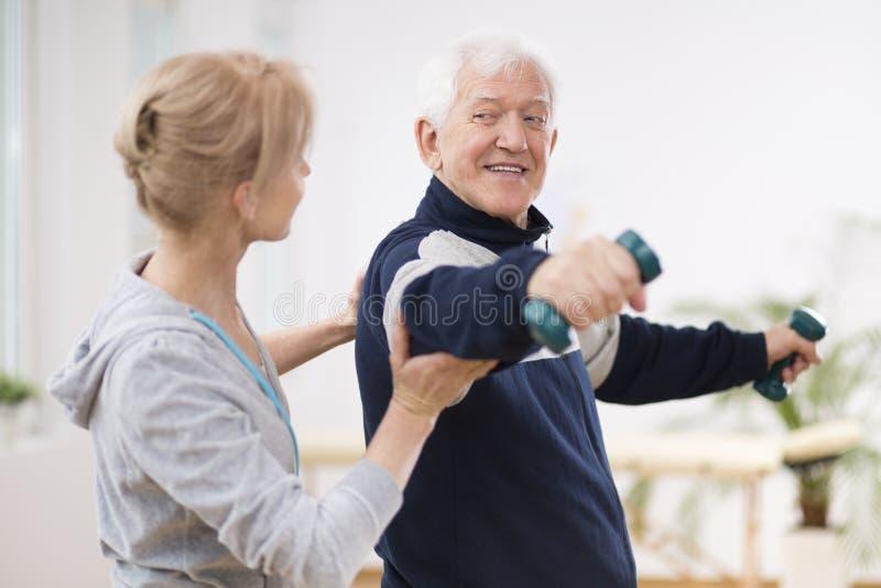 Senior nach dem Schlagmann am Pflegeheim trainierend mit Berufsphysiotherapeuten lizenzfreie stockbilder