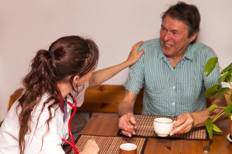 Senior and nurse having a conversation. Elderly men and nurse having a relaxed conversation stock image
