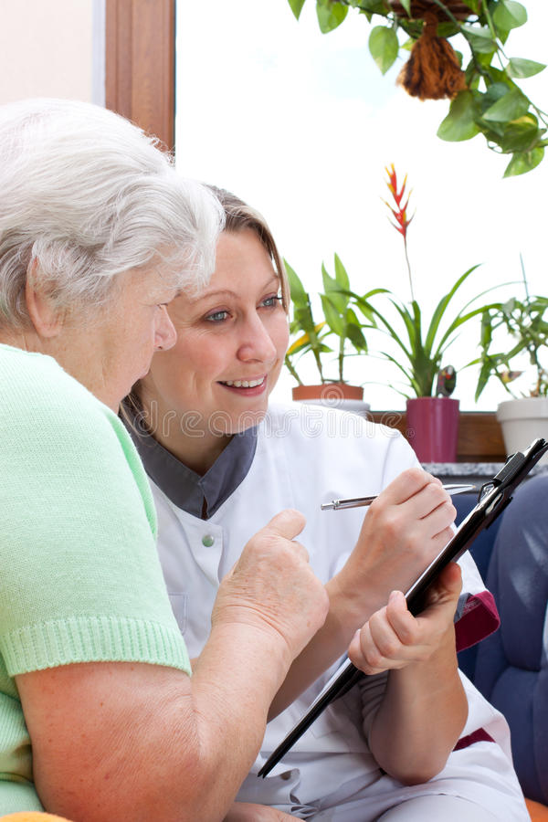 Senior and nurse sit together and write data royalty free stock photo
