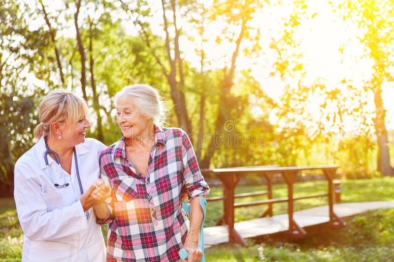 Senior with nursing assistant in the garden of the nursing home. Senior with nursing help in the garden of the nursing home in summer stock photo