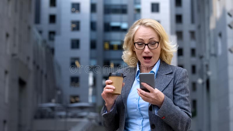 Senior office worker looking excited reading good news smartphone, business app royalty free stock photography