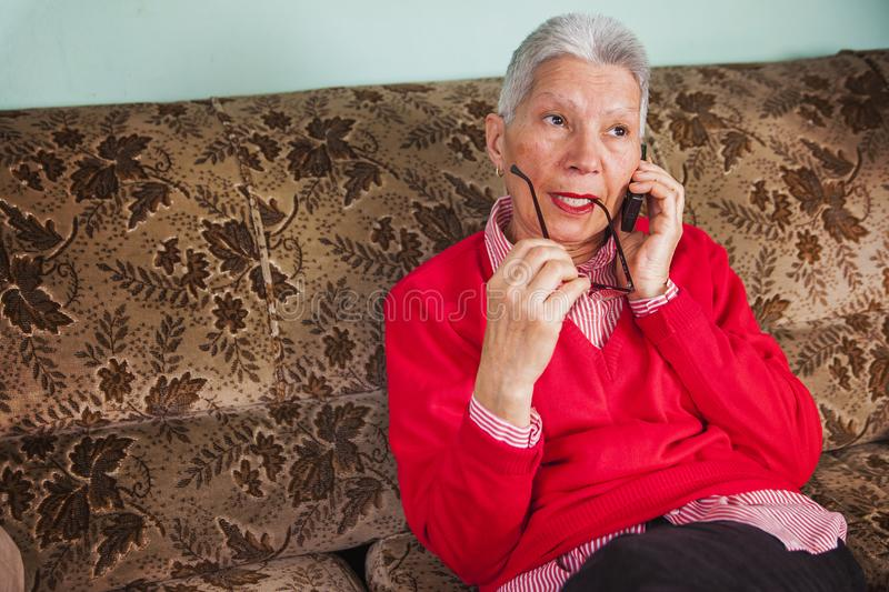What a boring conversation. Senior old woman having a boring conversation over her cellphone, chewing her spectacles royalty free stock image