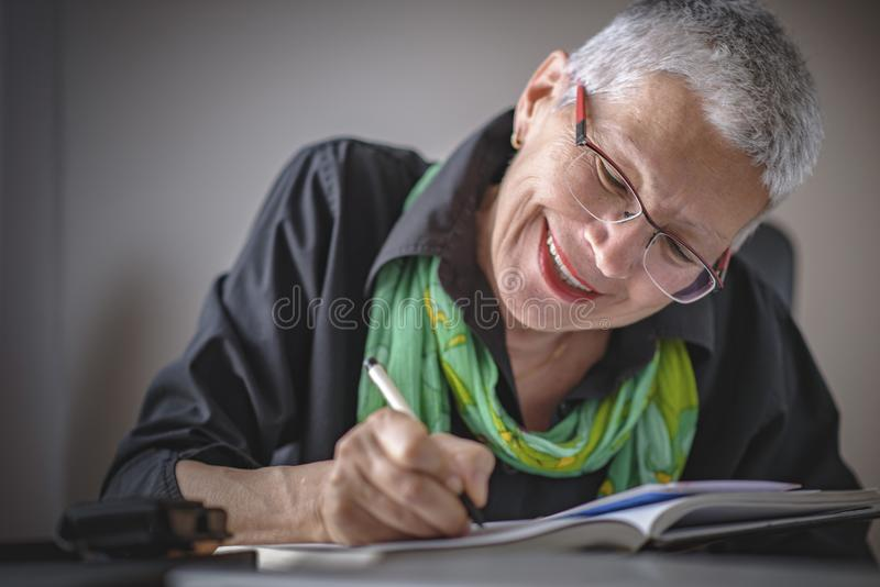 Writing an appointment in notebook. Senior old woman writing down letters on a piece of paper, recording a journal or diary entry or writing a novel royalty free stock image