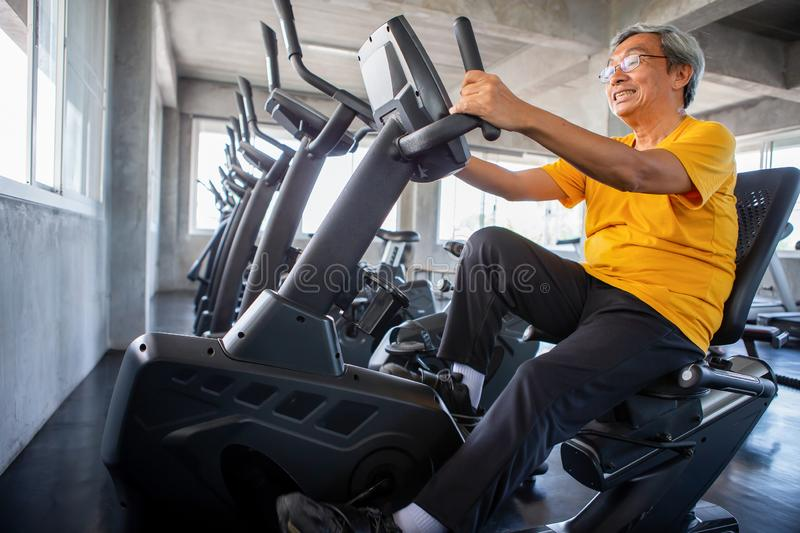 Senior older man exercising on cycling machine relaxing in fitness gym. aged . Old male workout .Mature sport training. stock photos