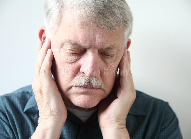 Senior with pain in front of ears. Older man holds both hands to his upper jaw near the ears royalty free stock image