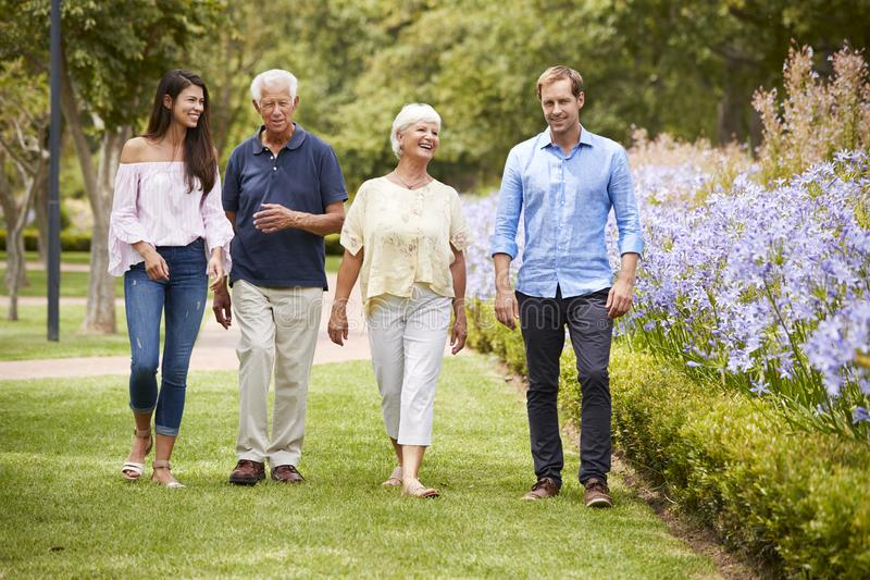 Senior Parents With Adult Children On Walk In Park stock photo