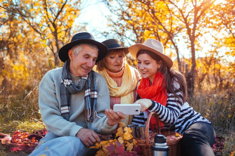 Senior parents using smartphone in autumn forest with their daughter. Family values. People having picnic. Together royalty free stock photography