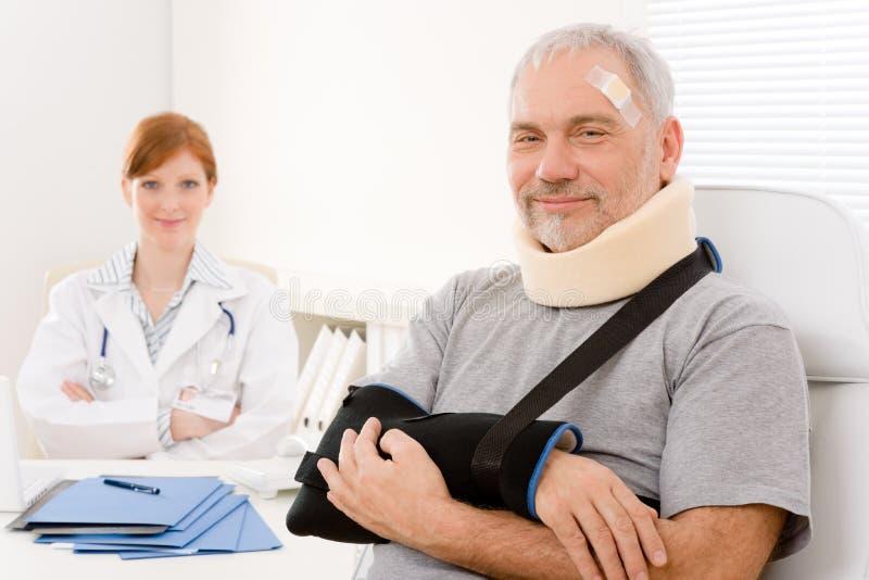 Senior patient broken arm in doctor office stock photo