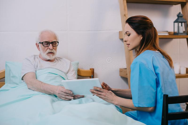 Senior patient and caregiver. Using tablet royalty free stock photos