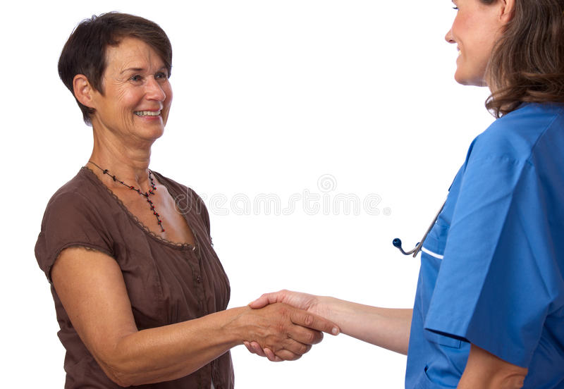 Senior patient greeting her doctor with handshake royalty free stock image