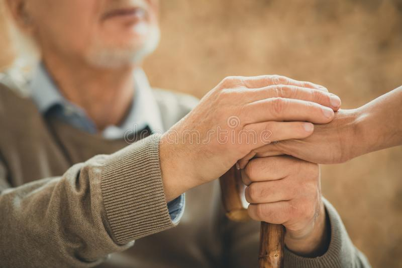 Senior patient and his doctor crossing their hands. Calming gesture. Senior patient and his doctor crossing their hands on the wooden stick stock photos