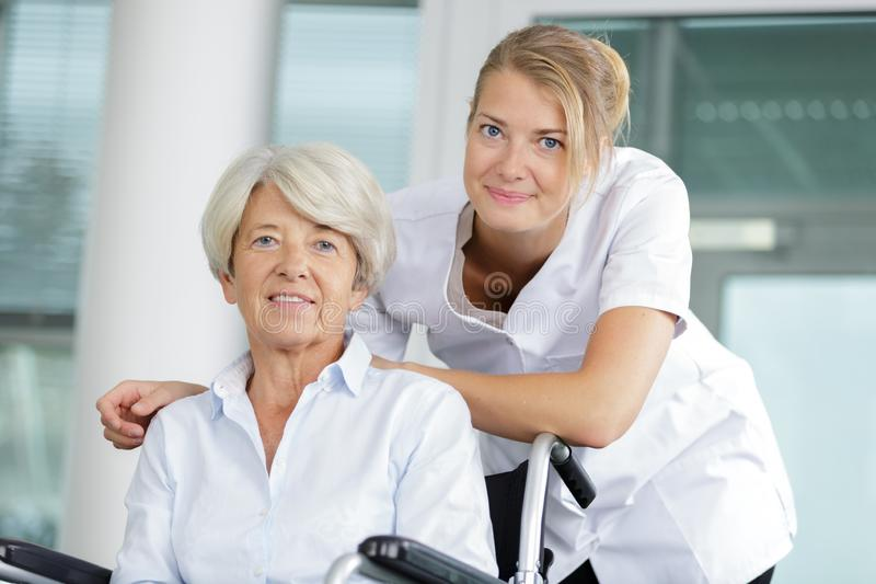 Senior patient in wheelchair with nurse. Woman royalty free stock images