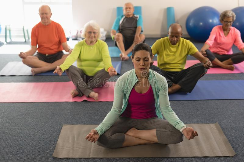 Senior people doing yoga with female trainer in fitness studio royalty free stock photo