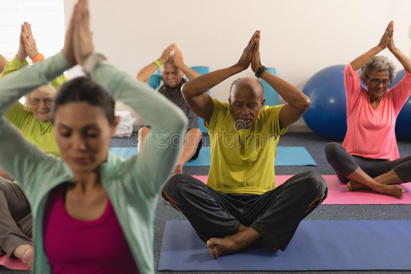 Senior people doing yoga with female trainer in fitness studio stock image