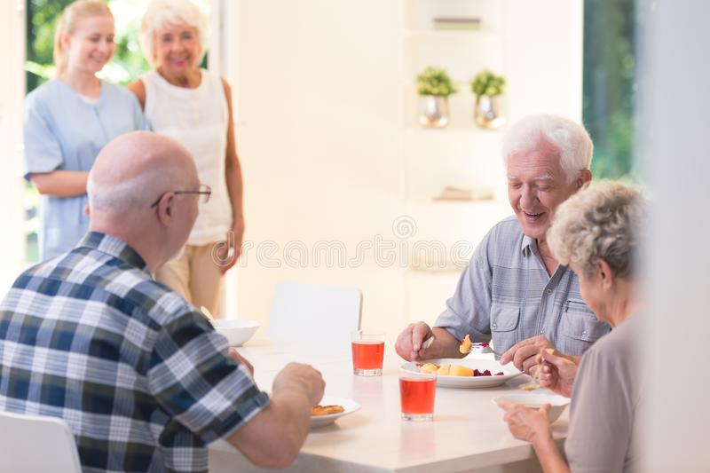 Senior people eating dinner. While sitting at a table in nursing house royalty free stock photography