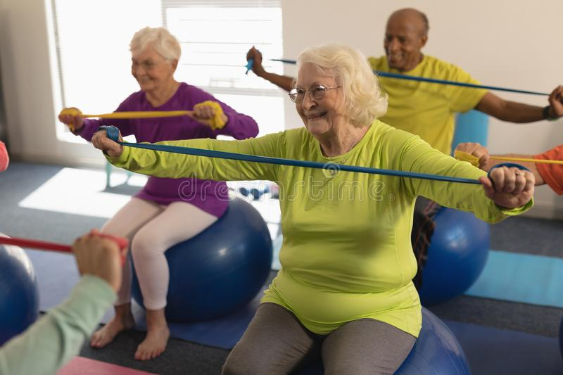 Senior people exercising with resistance band in fitness studio stock images