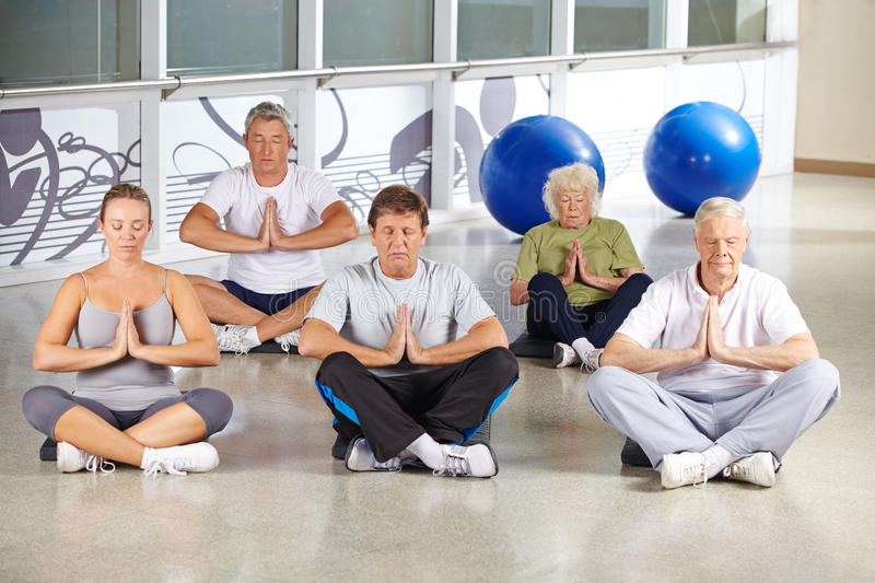 Senior people during meditation in yoga class royalty free stock photography