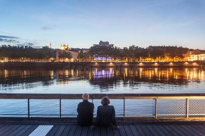 Senior people, and old couple of lovers, sitting on the quays of the riverbank of the rhone admiring the river during a summer. Picture of an old couple, senior stock photos