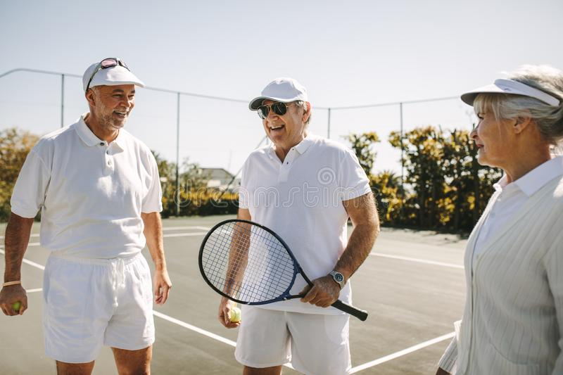 Senior men and a woman standing on a tennis court royalty free stock image