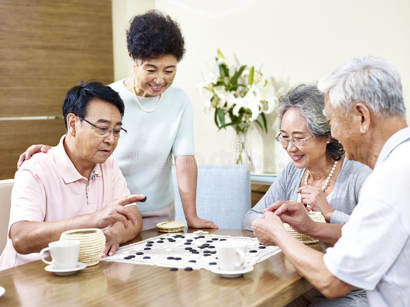 Senior people playing Weiqi at home royalty free stock image