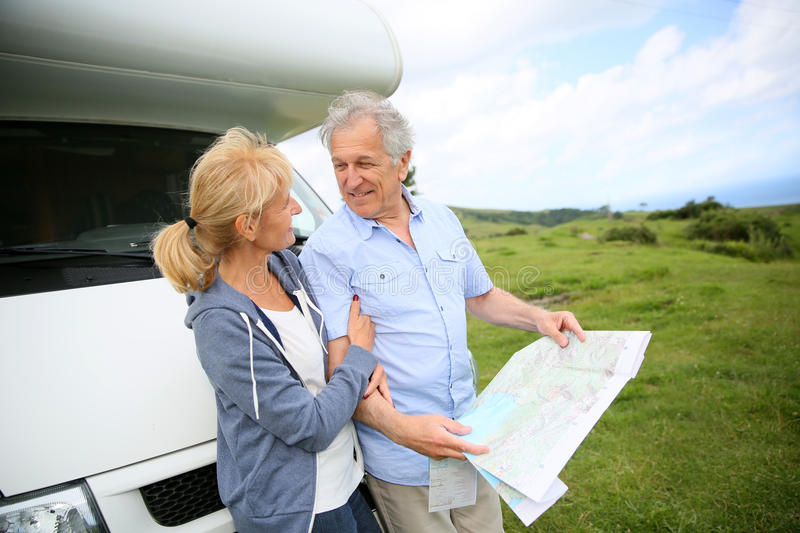 Senior people reading map stopping on roadtrip. Senior people reading road map by camper royalty free stock images