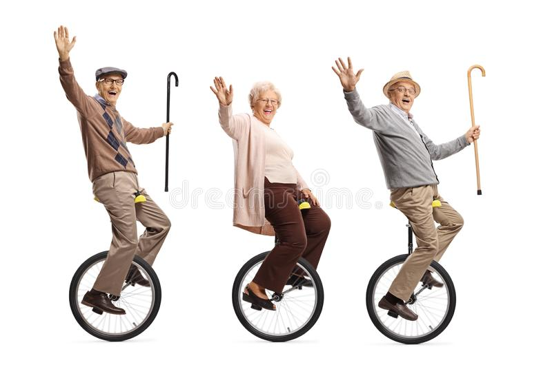 Senior people riding unicycles and smiling at the camera stock photos