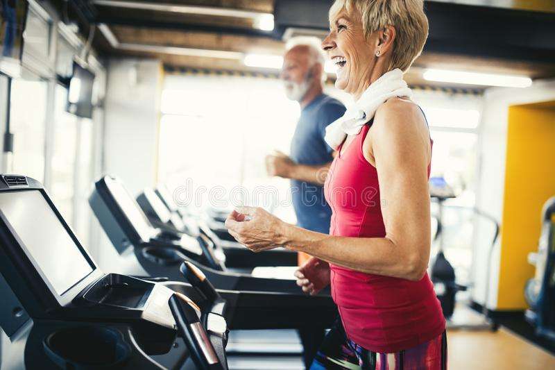 Senior people running in machine treadmill at fitness gym club royalty free stock images
