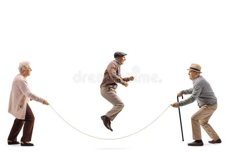 Senior people skipping a rope. Full length profile shot of senior people skipping a rope isolated on white background royalty free stock image