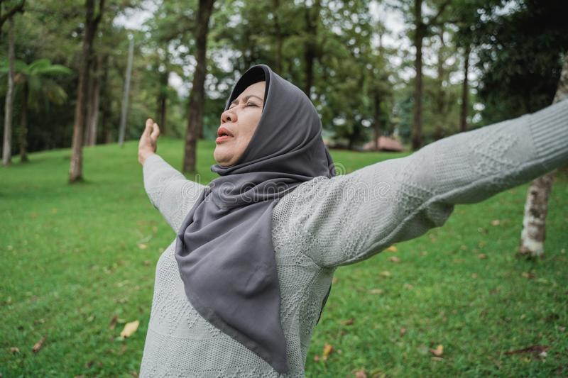 Senior people take a deep breath stretch out and raise arm. While in the park royalty free stock image