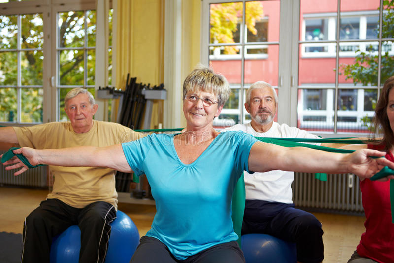 Senior people using latex band. Senior people in gym using latex band stock photography