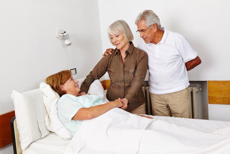Senior people visiting bedridden. Women in sickbed in a hospital royalty free stock image