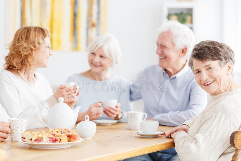 Senior people visiting old friends. Senior people visiting their old friends at home sitting together at wooden table chatting and drinking tea royalty free stock photos