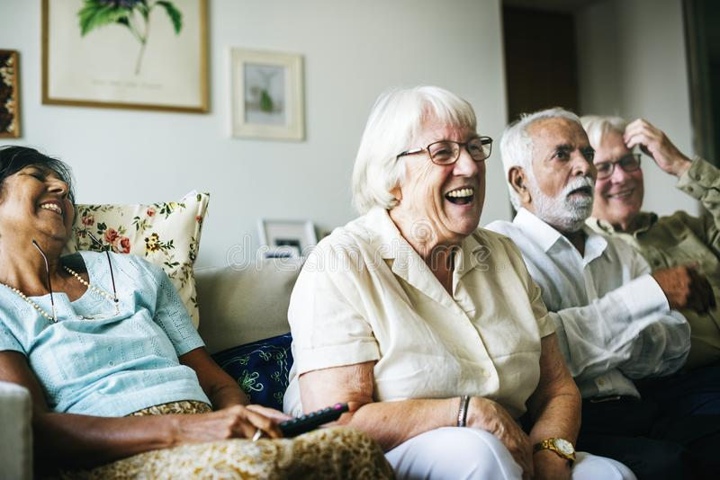 Senior people watching television together royalty free stock photo