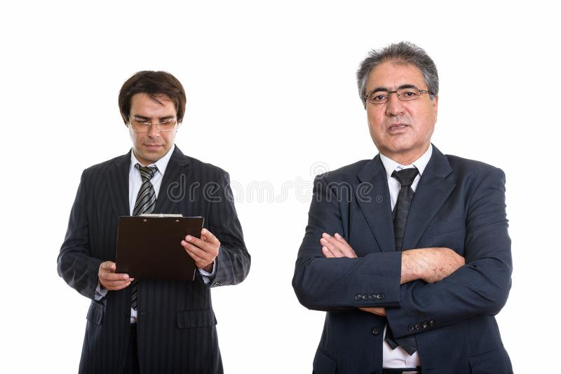 Senior Persian businessman with arms crossed and young Persian b. Usinessman reading on clipboard stock image