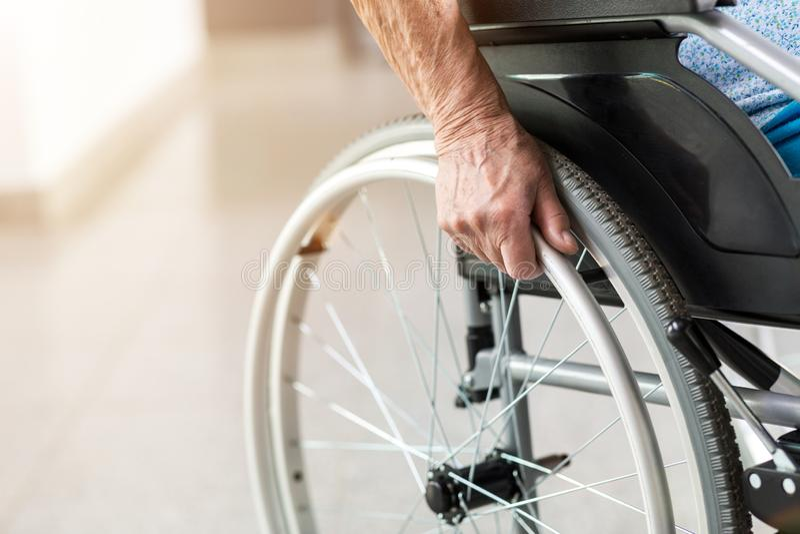 Senior person sitting in wheelchair. Unrecognizable senior person sitting in wheelchair royalty free stock photos