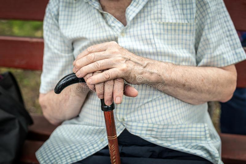 Senior person sitting on wooden bench outdoors. Old man hands ho. Lding walking stick. Poverty, loneliness and hopelessness concept royalty free stock photography