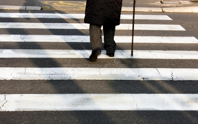 Senior person walking with a cane. Legs and shadow of a senior person using walking cane while crossing the street stock photography