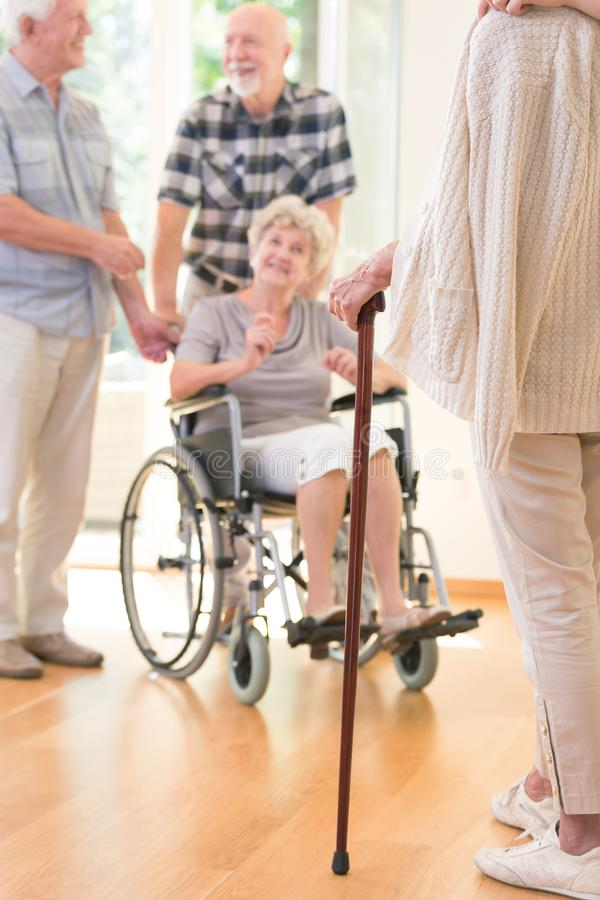 Senior person with walking stick. Senior person with a walking stick during meeting with friends in nursing house royalty free stock photography