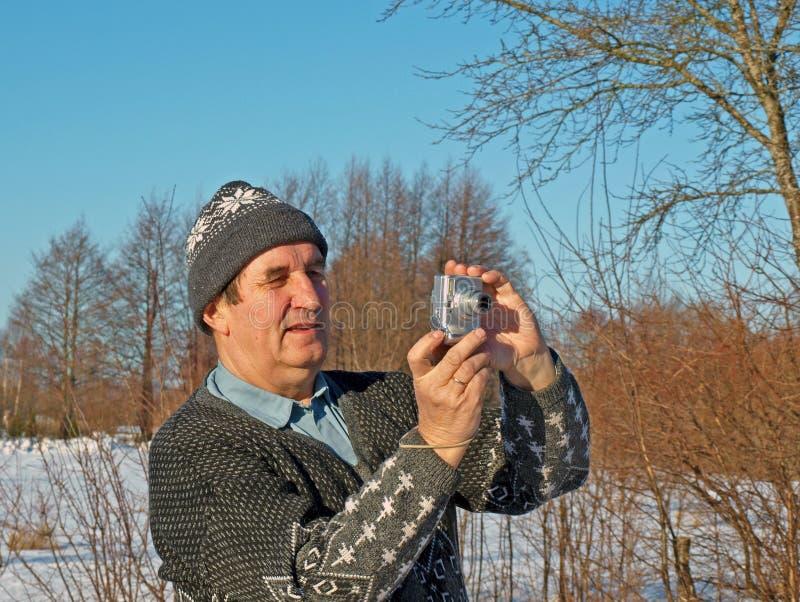 Senior photographer amateur 2. Senior man taking photos with cheap camera stock photo
