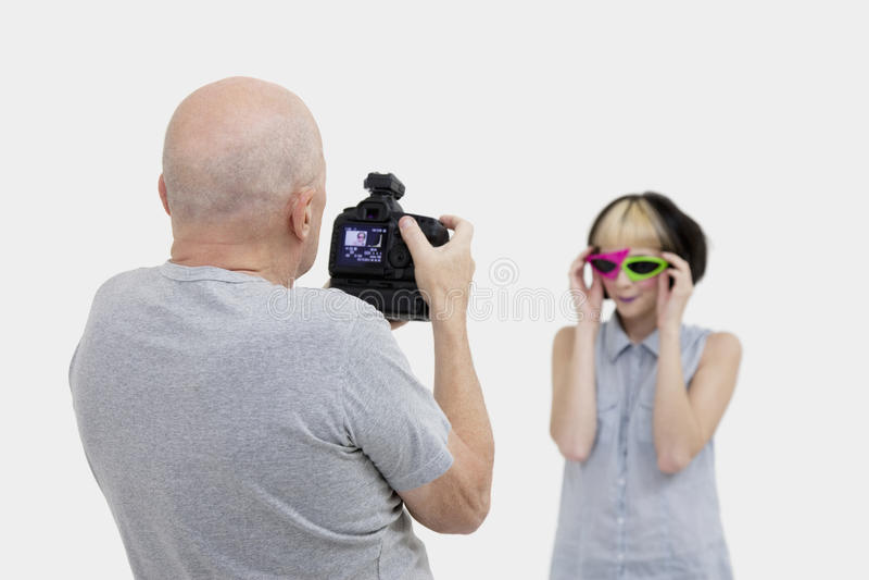 Senior photographer taking a photograph of fashion model during photo shoot stock image