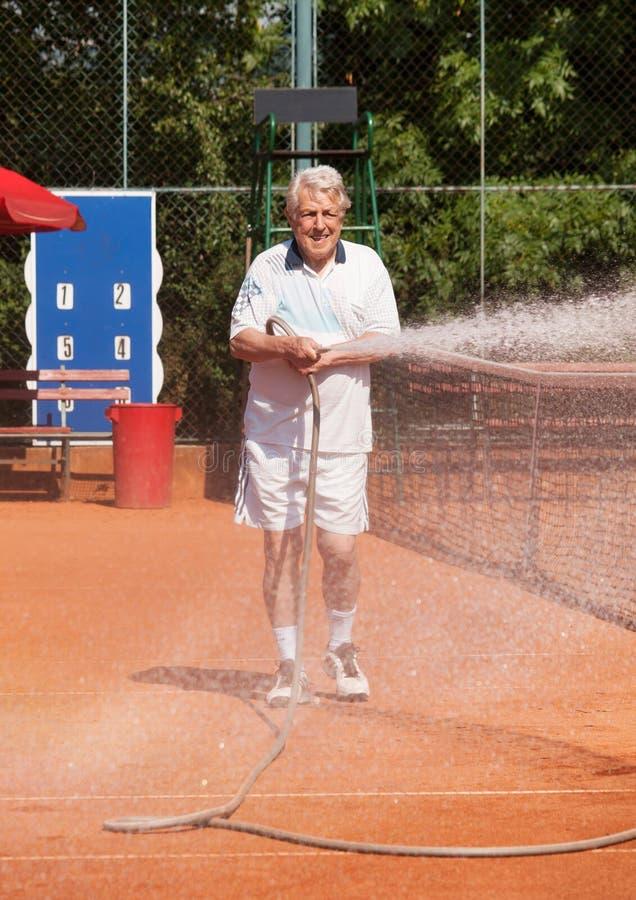 Senior player sprinkling tennis court. Senior man sprinkling tennis court before playing stock photo