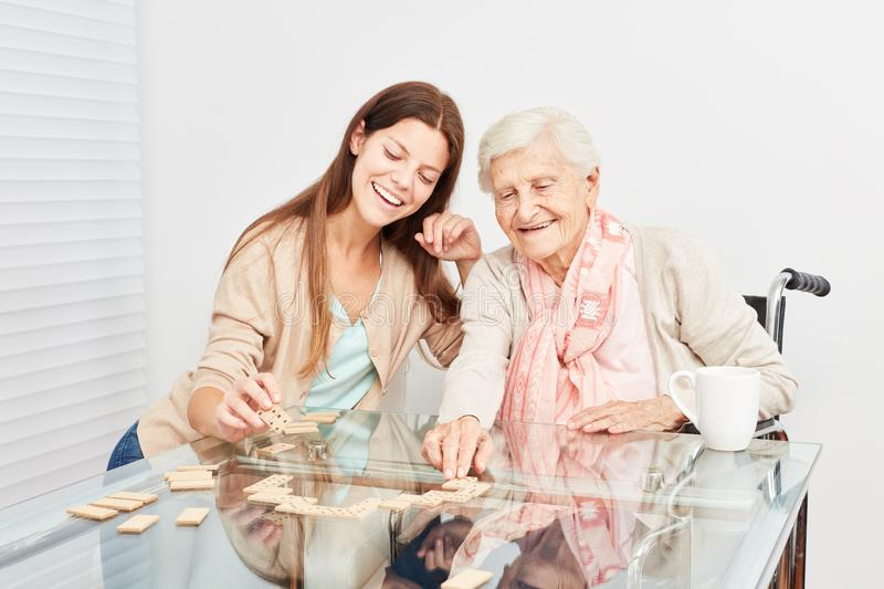 Senior plays with a care assistant Domino royalty free stock photography
