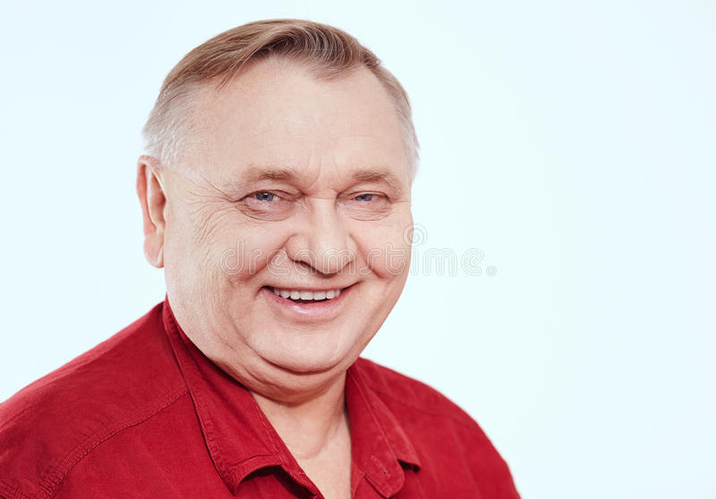 Senior portrait. Close up portrait of smiling aged man wearing red shirt against white background - retirement concept stock images